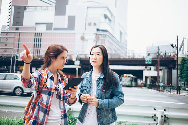Young woman asking for direction on street Young woman holding digital tablet on street and asking asian woman for direction. Wears casual clothes. City street and buildings on background. Shot taken during iStockalypse Kyoto 2016. boundary stock pictures, royalty-free photos & images