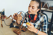 Young woman assembling wooden lamp in carpentry workshop