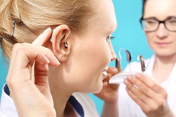 young woman assumes a hearing aid - hearing loss stock pictures, royalty-free photos & images