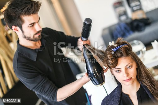 Attractive young woman at a hair salon with male hairdressers styling her hair. Both of them about 25 years old, Caucasian people.