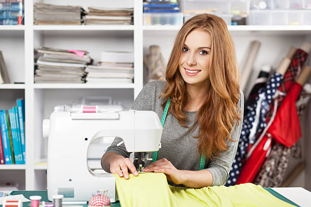 Young woman at a sewing machine stock photo