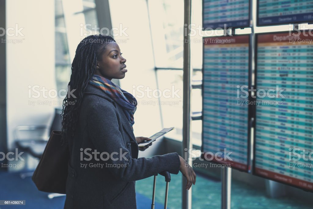 Young woman at airport Young African American woman at airport checks the arrivals and departures board 20-29 Years Stock Photo