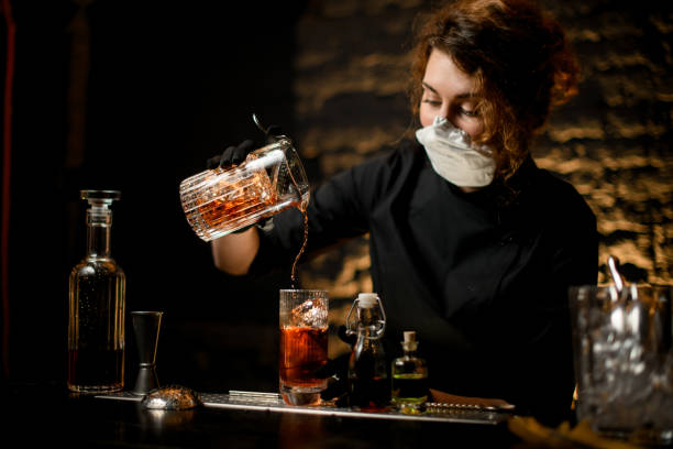 young woman at bar accurate pours cold cocktail into glass. young woman in medical mask and black gloves stands at bar and accurate pours cold cocktail into glass. bartender stock pictures, royalty-free photos & images
