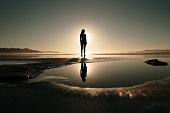 Young woman at a beach at sunset and her reflection on a puddle