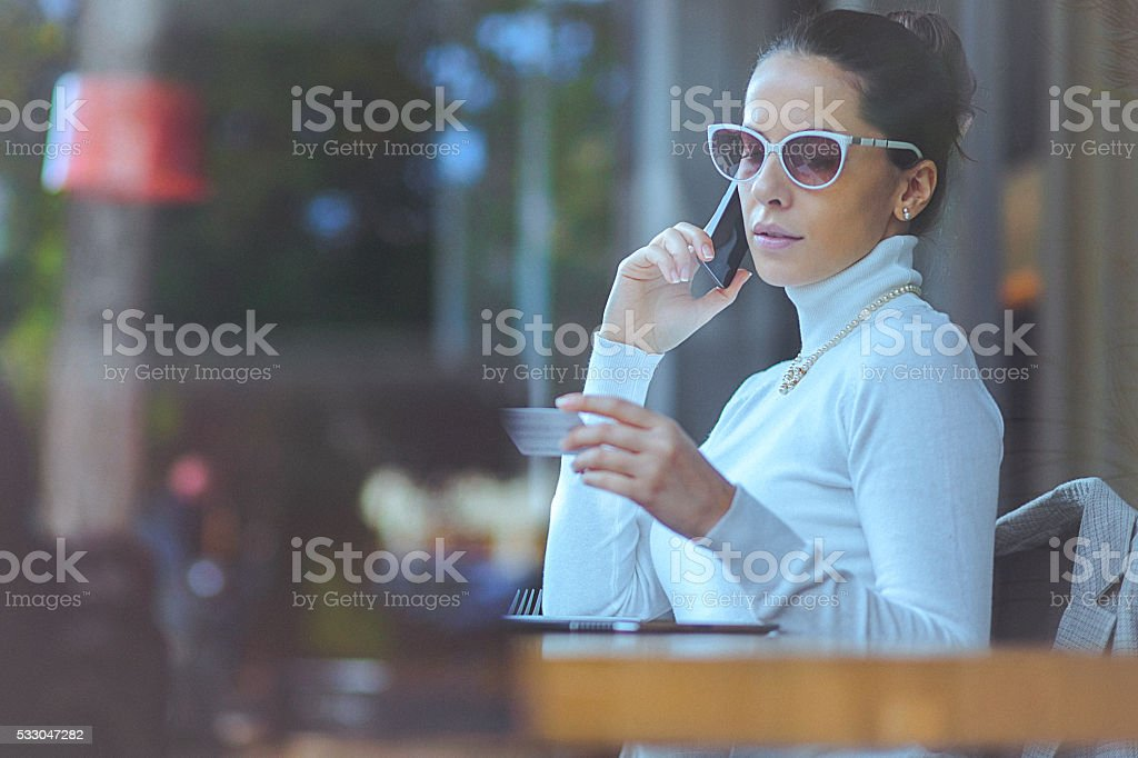 Young woman at cafe using credit card for online transaction stock photo