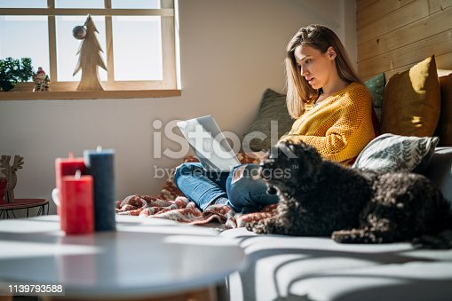 Relaxed Woman at Cozy Home Purchasing Online while Cute Dog Sitting next to Her