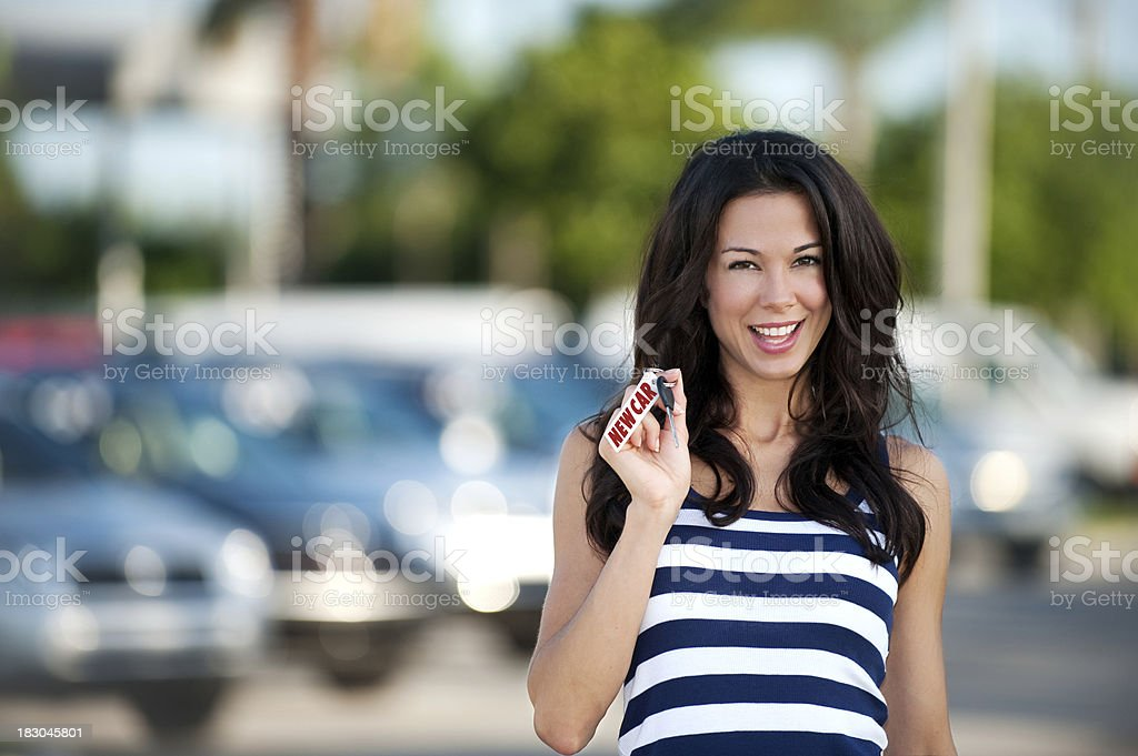 Young Woman at Dealership with New Car Key royalty-free stock photo