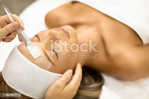 Young woman receiving beauty treatment with face cream and moisturizer in beauty and spa center. She is young and beautiful, with perfect skin