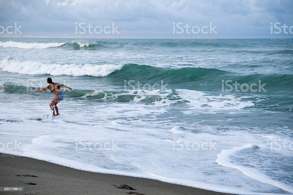 Young woman at Florida beach with skimboard stock photo