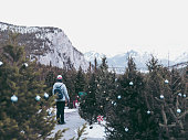 young woman at garden with Christmas decorated pine trees, banff national park, canada.