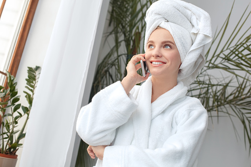 610769340 istock photo Young woman at home beauty care standing talking with friend on smartphone happy 1170007584