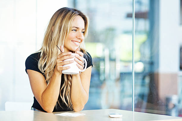 young woman at home drinking coffee stock photo