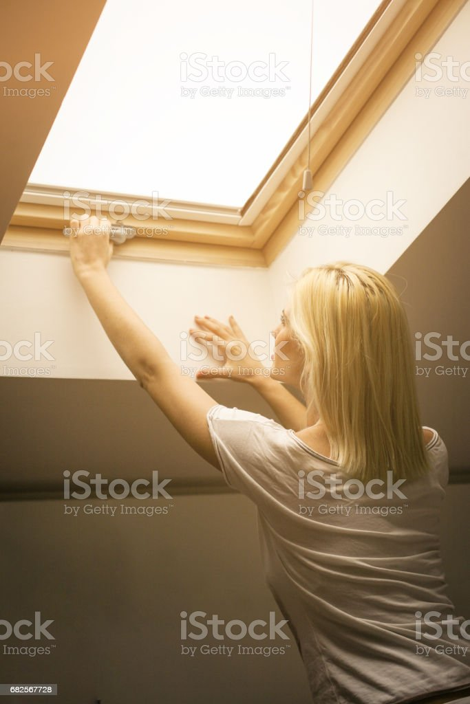 Young woman at home. Girl opens window. stock photo