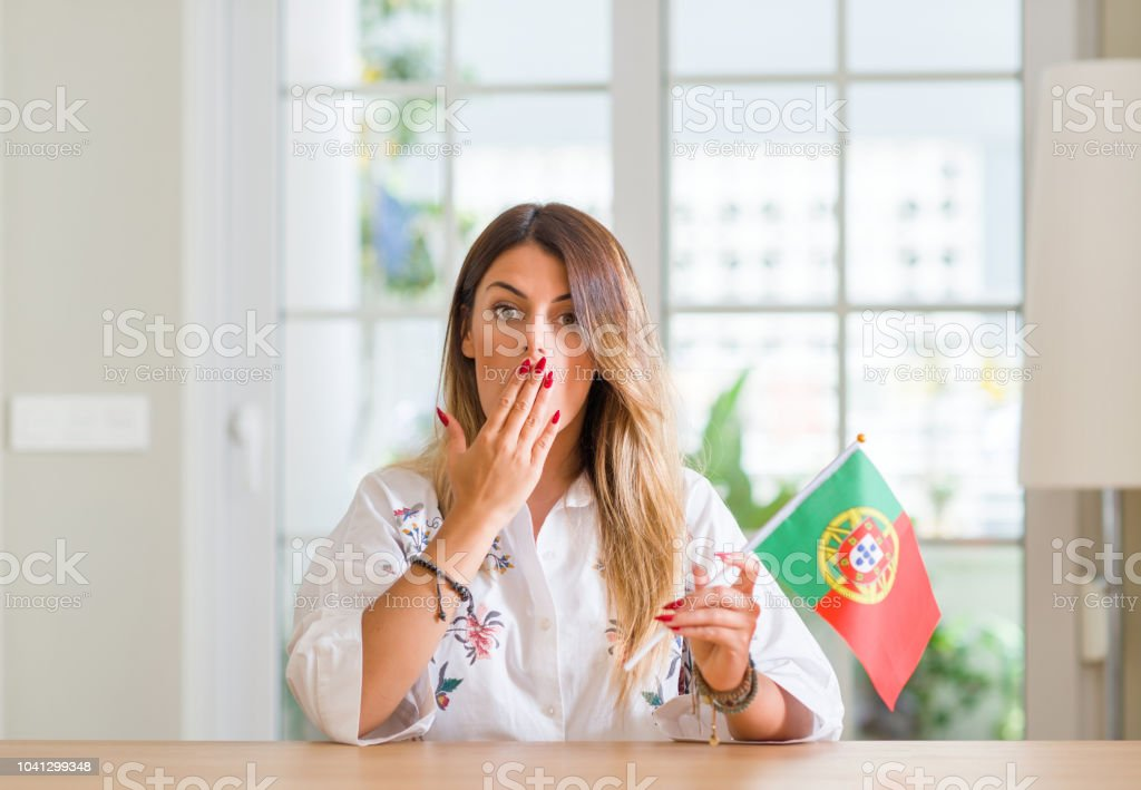 Young woman at home holding flag of Portugal cover mouth with hand...