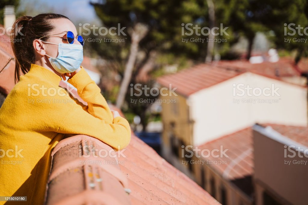 young woman at home on a terrace wearing protective mask and enjoying a sunny day. Corona virus Covid-19 concept young woman at home on a terrace wearing protective mask and enjoying a sunny day. Corona virus Covid-19 concept Adult Stock Photo