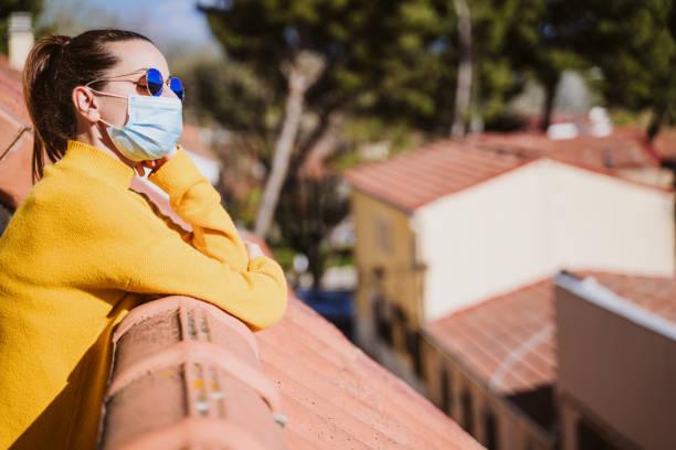 joven en casa en una terraza con máscara protectora y disfrutando de un día soleado. Virus Corona Concepto Covid-19 - foto de stock