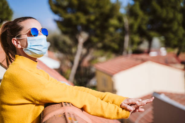 young woman at home on a terrace wearing protective mask and enjoying a sunny day. Corona virus Covid-19 concept stock photo