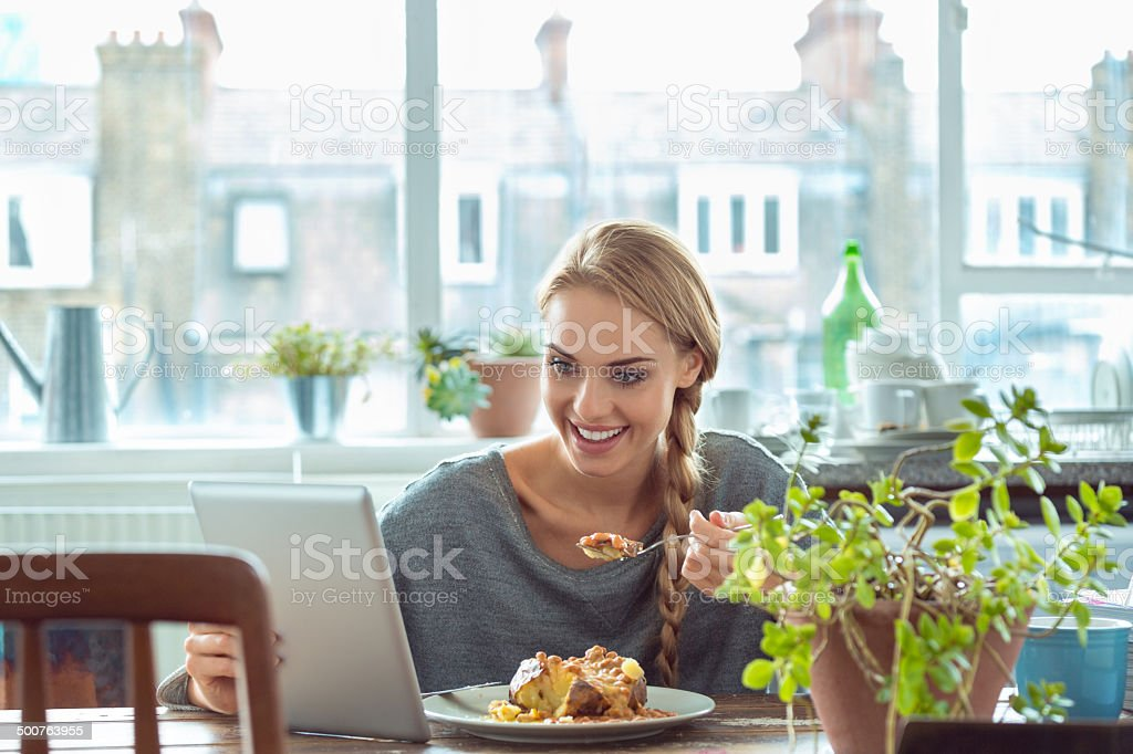 Young woman at home Young woman sitting at the table in the kitchen at home, eating a jacket potato with beans and cheese and using a digital tablet. 20-24 Years Stock Photo