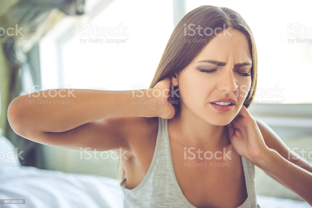 Young woman at home Beautiful young woman in gray singlet is keeping hands on her neck, feeling pain, sitting on bed at home Adult Stock Photo