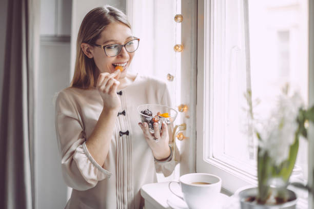 young woman at home - dried fruit stock photos and pictures