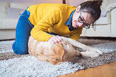 Young woman at home playing with dog