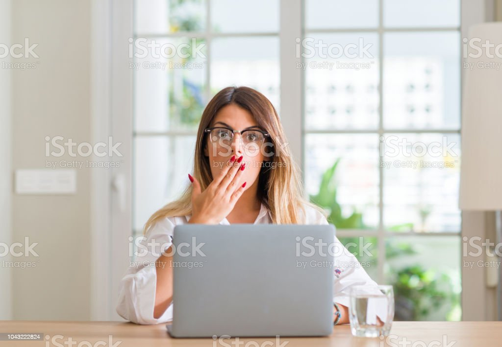 Young woman at home using laptop cover mouth with hand shocked with...