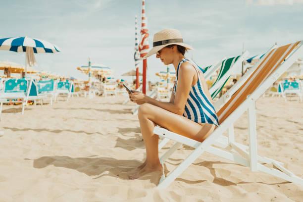 junge frau am italienischen strand - outdoor sonnenschutz stock-fotos und bilder