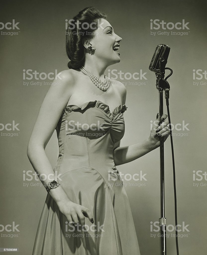 Young woman at microphone, singing, (B&W) stock photo