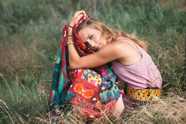 junge frau beim musikfestival unter einem baum ausruhen - hippie kleider stock-fotos und bilder