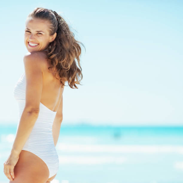 young woman at seaside young woman at seaside middle aged women in bikinis stock pictures, royalty-free photos & images