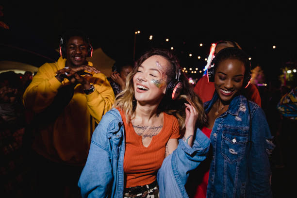 Young Woman at Silent Disco Young woman is dancing in a silent disco with her friends. disco dancing stock pictures, royalty-free photos & images