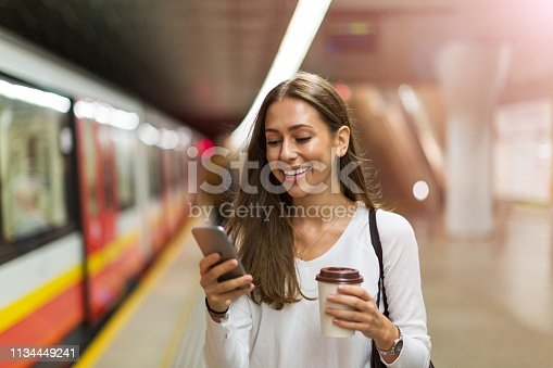 Woman using mobile phone at subway station