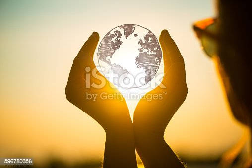 istock young woman at sunset holding planet earth in her hands 596780356