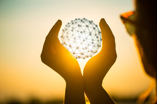 istock young woman at sunset holding sphere network in her hands 601357334