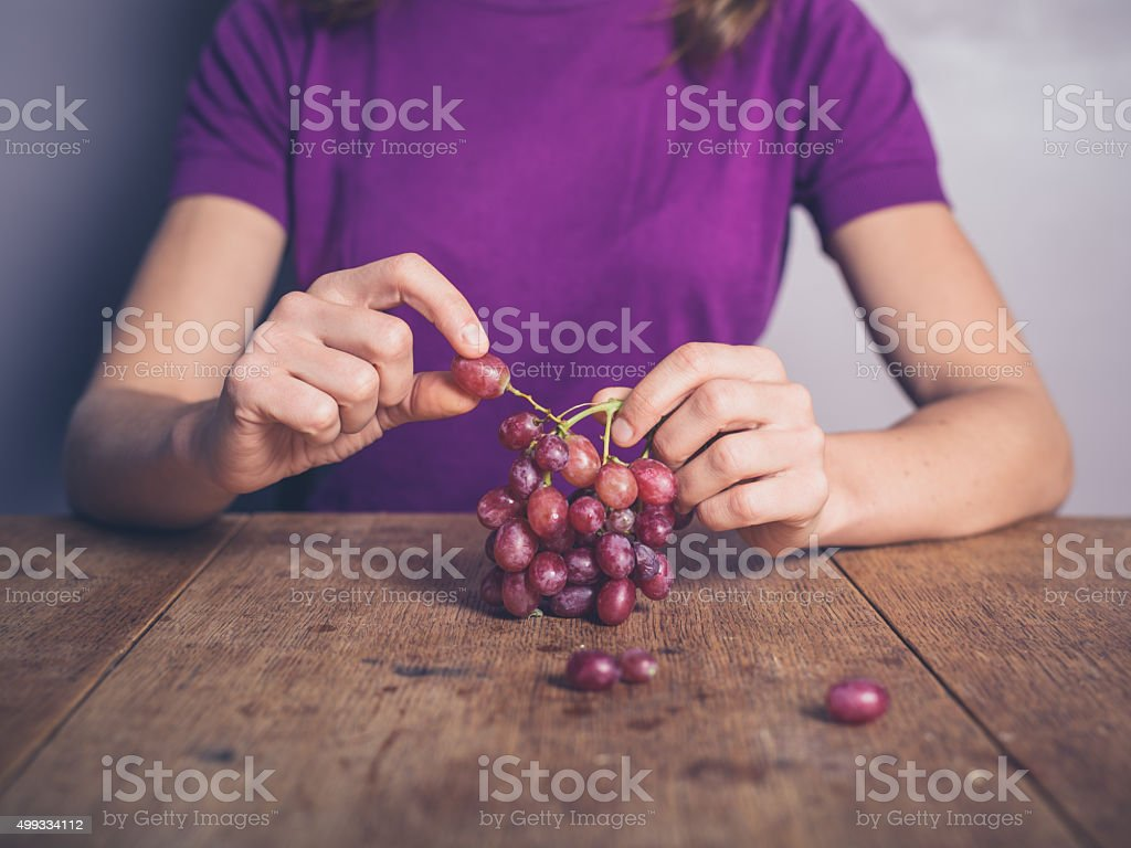 Young woman at table eating grapes stock photo