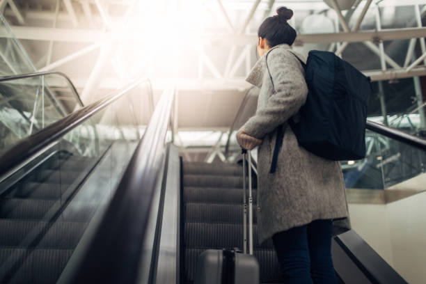 young woman at the airport, on the escalator - hand luggage stock pictures, royalty-free photos & images