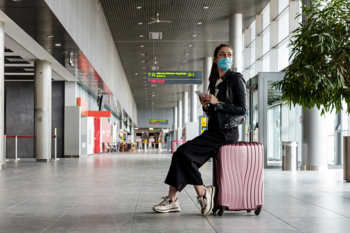 People traveling by plane during COVID 19. Young woman wearing N95 face masks, sitting on luggage in airport terminal, holding smart phone.