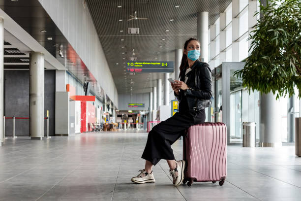 Young woman at the airport with luggage, wearing N95 face masks stock photo
