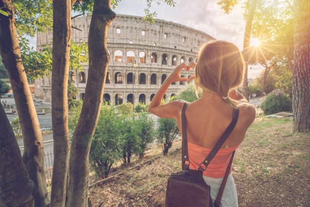 Young woman at the Colosseum in Rome making a heart shape finger frame with hands loving travel in Italy stock photo