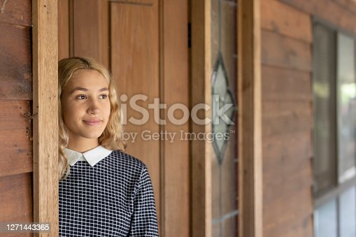 istock Young woman at the front door of a house 1271443365