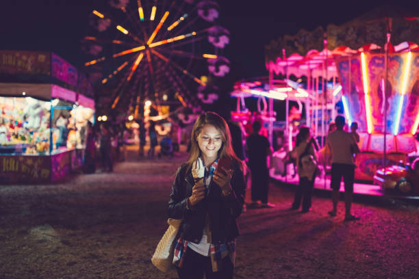 Young woman at the funfair text messaging Smiling girl texting at the amusement park traveling carnival stock pictures, royalty-free photos & images