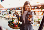 A young woman at the green market shopping for vegetables, looking at the shopping list on her phone.