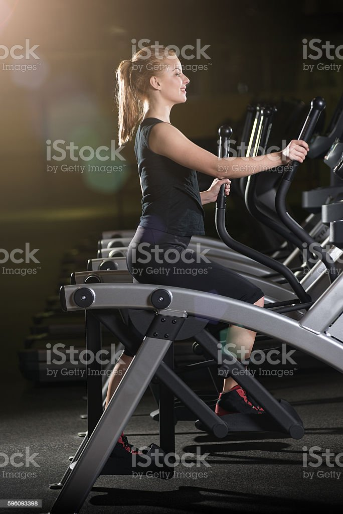 Young woman at the gym exercising. Run on machine. royalty-free stock photo