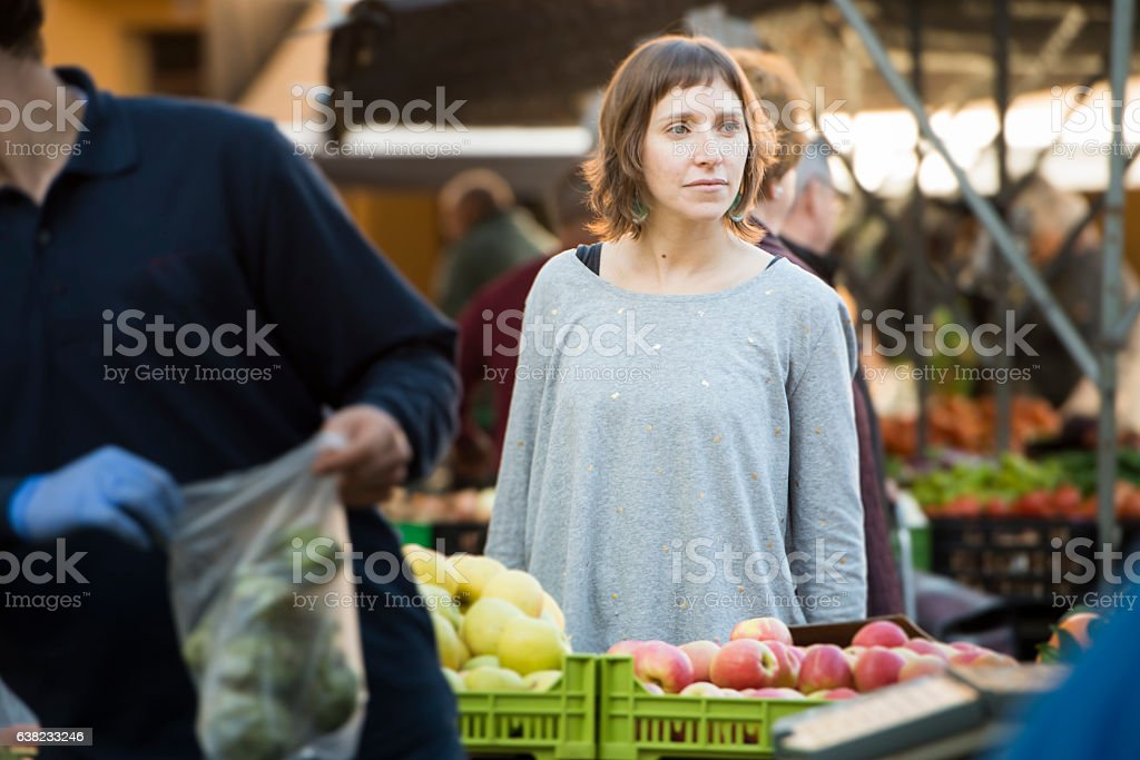 Young woman at the organic farmer'smarket Young woman from Mallorca, Spain, buying at farmer's market organic food for a healthy eating lifestyle. Adult Stock Photo