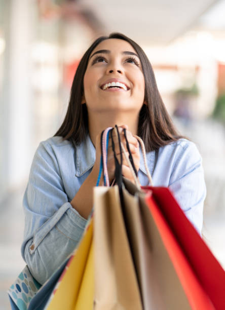 Young woman at the shopping mall holding her bags and looking up very grateful stock photo