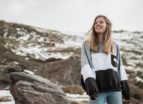 Young woman at the top of the mountain with snow smiling and happy. Cold weather