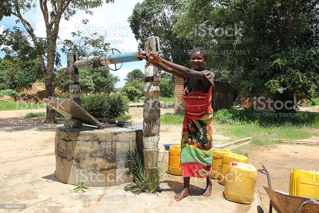 Young Woman at the water well in Africa stock photo