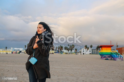 Retro toned portrait of a young traveler woman, walking and enjoying the vast, beautiful Venice Beach in Los Angeles, California. She is posing next to the rainbow colored Pride lifeguard hut.