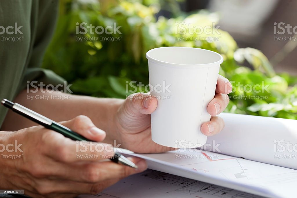 Young woman at work drinking coffee from disposable cup. stock photo