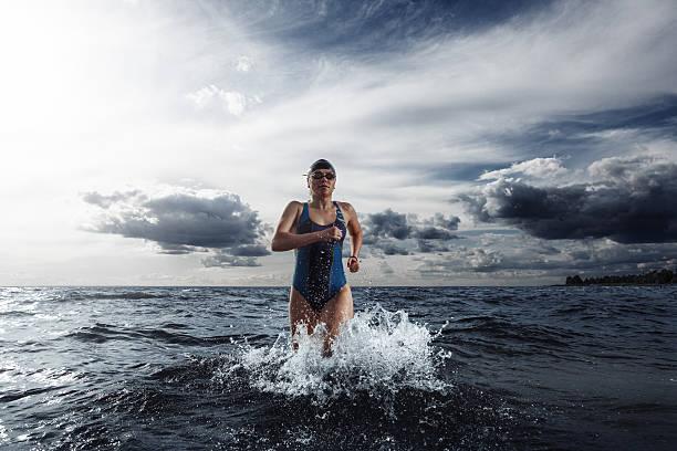 Mujer joven atleta corriendo fuera del agua - foto de stock